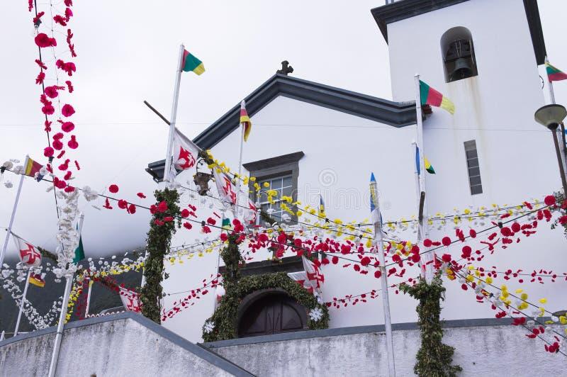 Des fleurs rouges et jaunes ornent l'extérieur d'une église blanche aux drapeaux colorés de Madère, Portugal images libres de droits