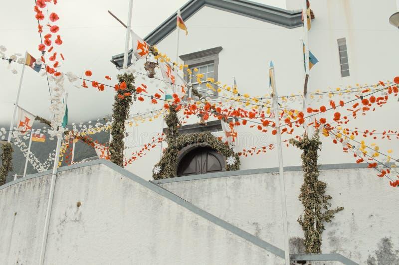 Des fleurs rouges et jaunes ornent l'extérieur d'une église blanche aux drapeaux colorés de Madère, Portugal photos stock