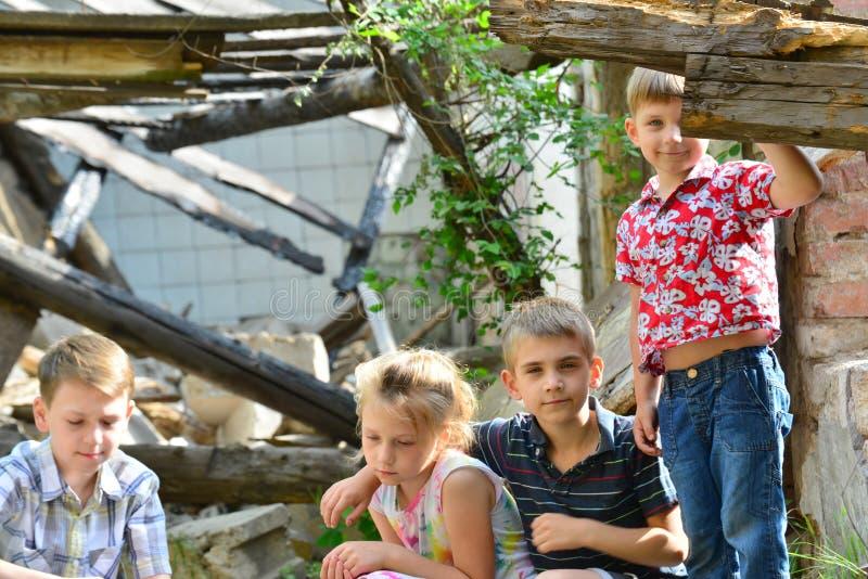 Des frères et les orphelines de soeurs ont été laissés sans loger et se tiennent près des ruines du bâtiment en raison du conflit image libre de droits