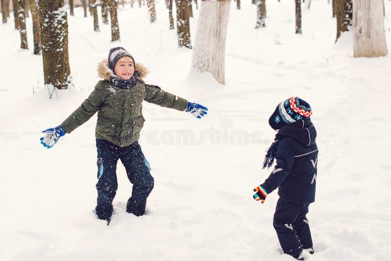 Des frères heureux qui jouent avec la neige Fêtes d'hiver et de Noël Temps froid enneigé Vacances d'hiver en plein air Joyeux frè photos libres de droits