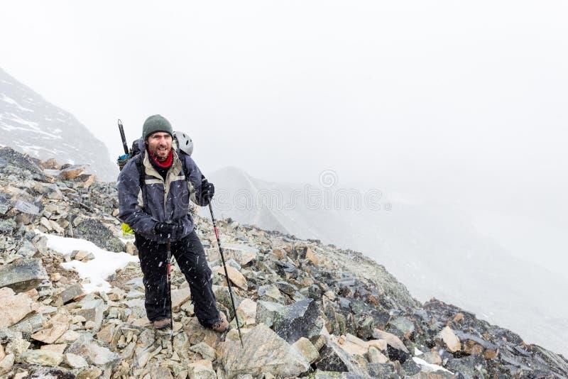 Des Gebirgspfad-Sturms des Bergsteigers touristisches gehendes schneiendes Wetter lizenzfreie stockfotos