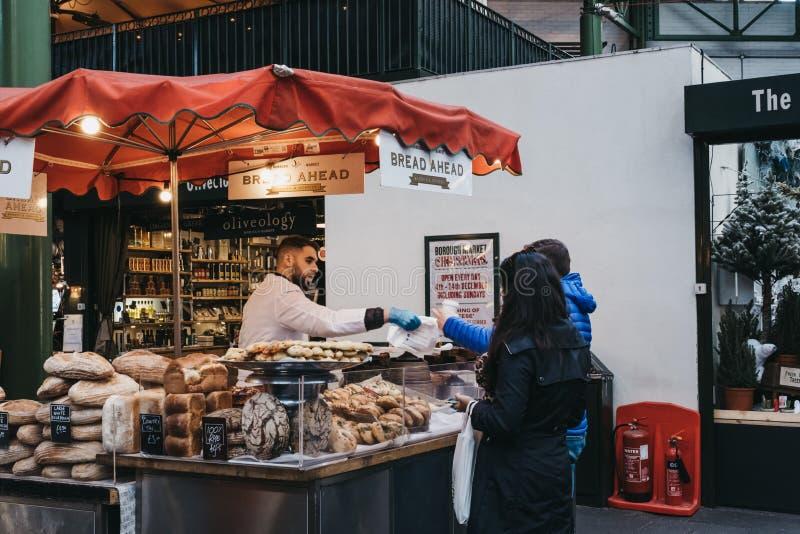 Des gens achètent du pain et des pâtisseries dans le magasin Bread Ahead à Borough Market, Londres, Royaume-Uni image stock