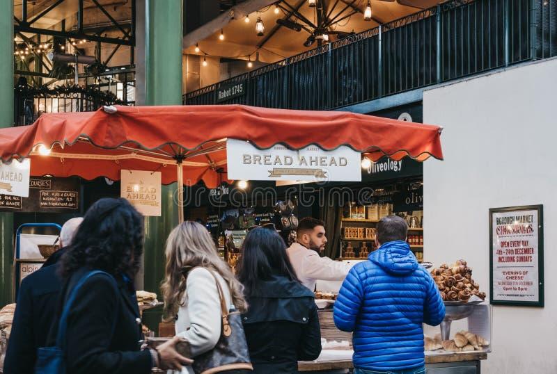 Des gens achètent du pain et des pâtisseries dans le magasin Bread Ahead à Borough Market, Londres, Royaume-Uni photo libre de droits