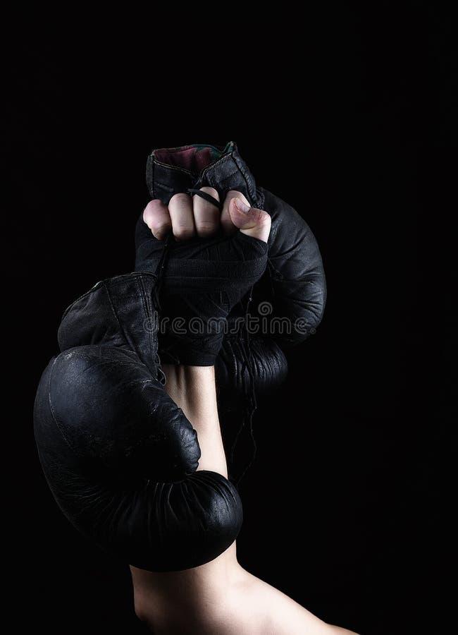 Des gezüchteten die Hand oben Mannes hält ein Paar alte schwarze lederne Boxhandschuhe stockfotografie