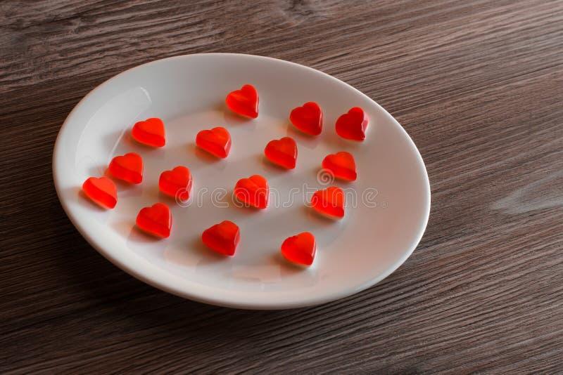 Des gummiartigen kleines kleines Tonwarenkonzept Geleeherzens des Valentinstagfeiertags Übersteigen Sie über obenliegendem Ansich stockbild