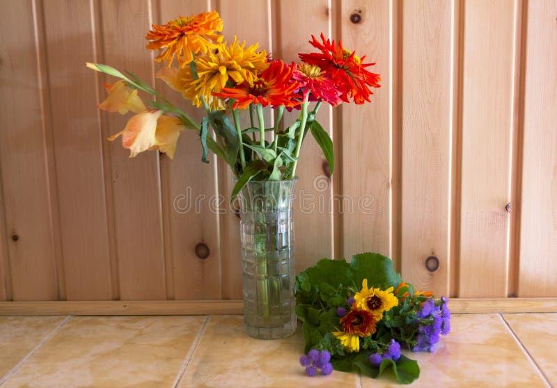 Des Herbstes Leben noch ein Blumenstrauß von Blumen in einem Vase und von Lügen nahe bei einem anderen Blumenstrauß auf dem Hinte stockfoto