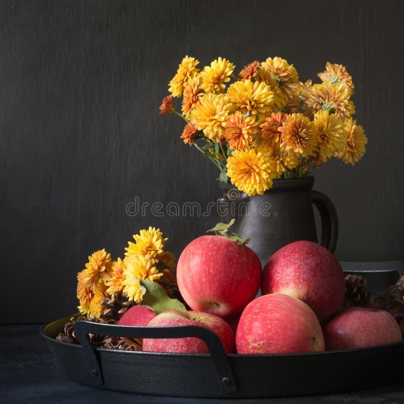 Des Herbstes Leben noch Fallernte mit Äpfeln, gelbe Blumen im Vase auf Dunkelheit stockfoto