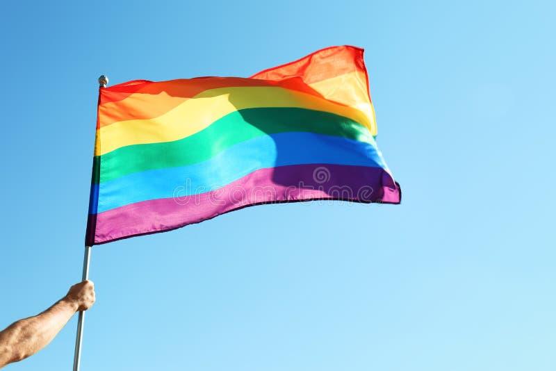 Des Holdingregenbogens LGBT des homosexuellen Mannes Flagge lizenzfreie stockbilder
