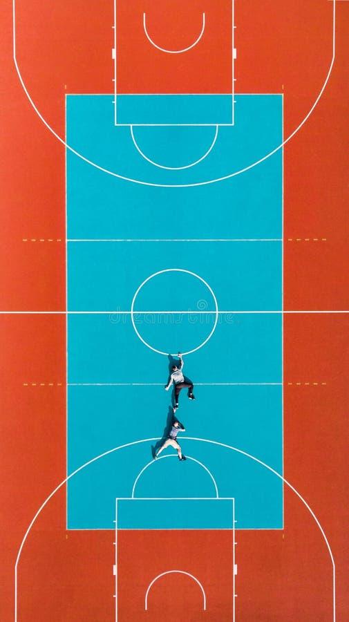 Des hommes accrochés à la ligne de terrain de basket-ball, image d'illusion créative et amusante image stock