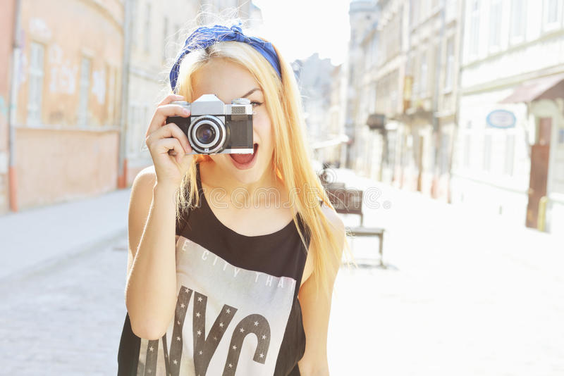 Des im Freien lächelndes Lebensstilporträt Sommers der recht jungen Frau, die Spaß in der Stadt in Europa mit Kamera hat Reisefot stockbilder