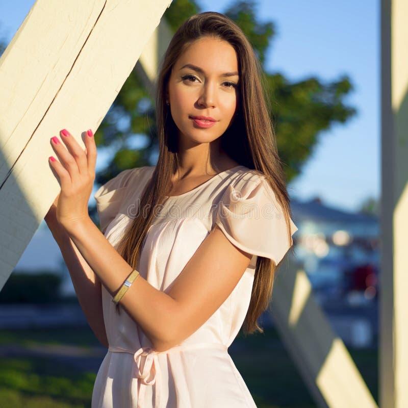 Des im Freien sinnliche stilvolle junge Frau Modeporträtzaubers, die einen Sommerkleiderbonbon, Brunettemädchen trägt Rosa, rot lizenzfreie stockfotos