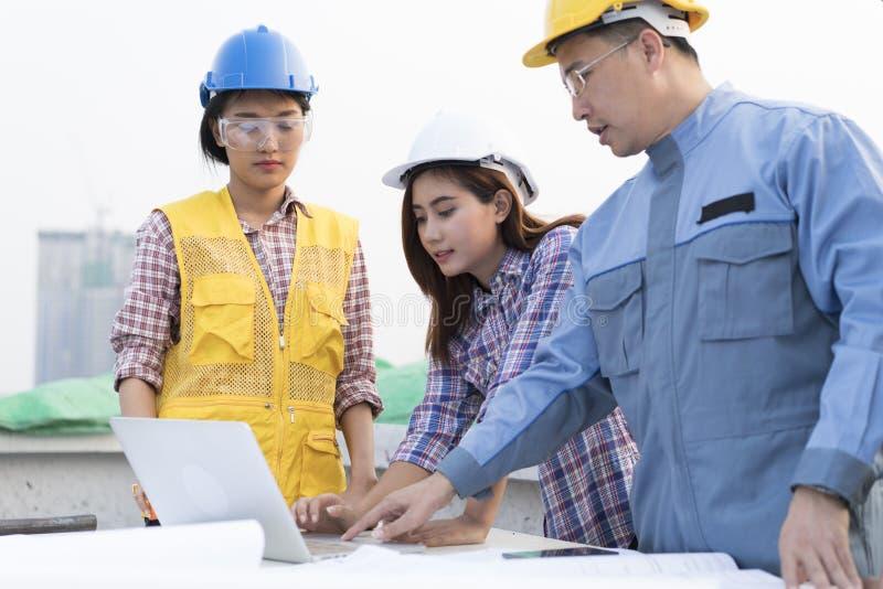 Des ingénieurs asiatiques ont été consultés ensemble et prévoient dans la construction photographie stock libre de droits