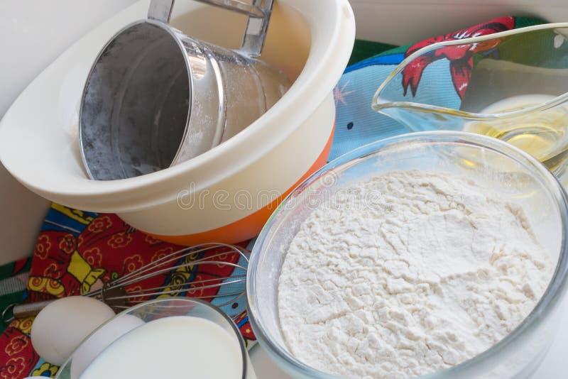 Des ingrédients crus pour des crêpes sont présentés sur une nappe multicolore images libres de droits