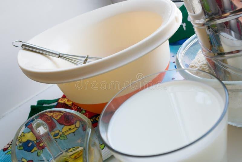 Des ingrédients crus pour des crêpes sont présentés sur une nappe multicolore et un fond blanc images libres de droits