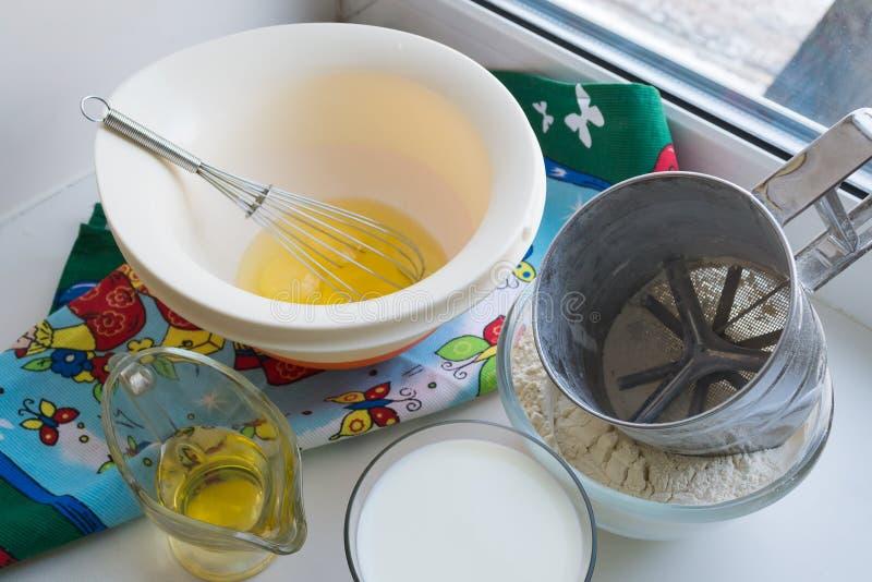 Des ingrédients crus pour des crêpes sont présentés sur une nappe multicolore et un fond blanc image stock