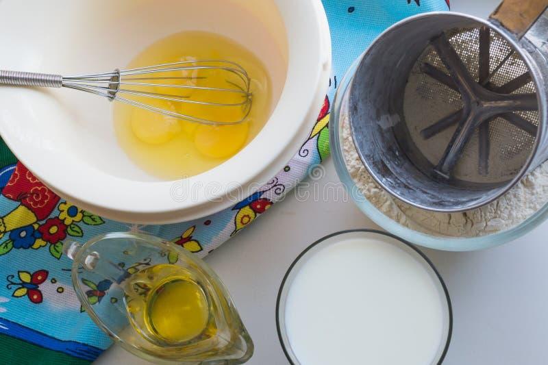 Des ingrédients crus pour des crêpes sont présentés sur une nappe multicolore et un fond blanc photographie stock