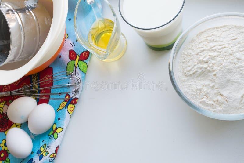 Des ingrédients crus pour des crêpes sont présentés sur une nappe multicolore et un fond blanc et copient l'espace photos libres de droits