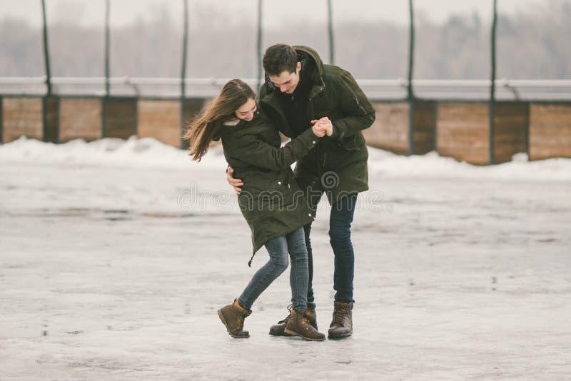 Des jeunes de couples hétérosexuels dans des étudiants d'amour un homme et une femme caucasienne En hiver, dans la place de ville images stock