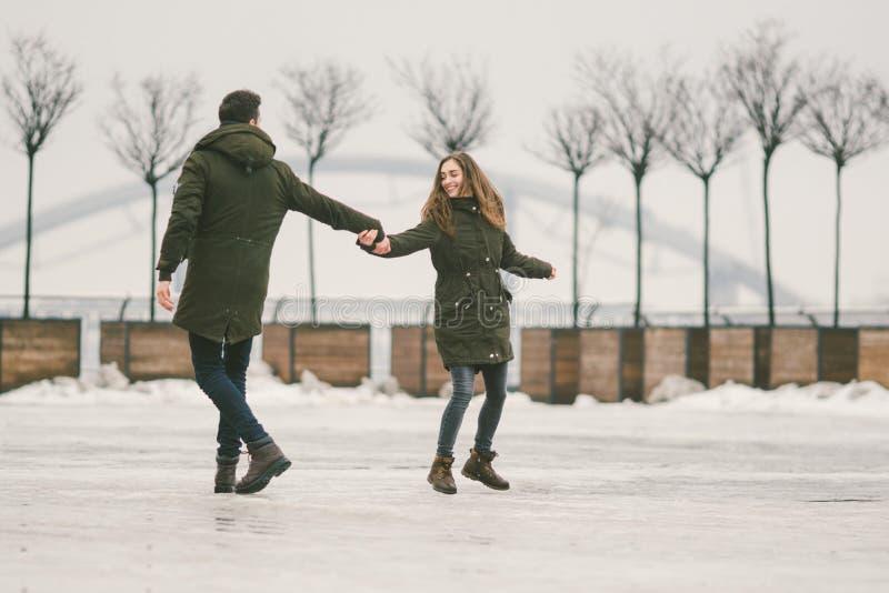 Des jeunes de couples hétérosexuels dans des étudiants d'amour un homme et une femme caucasienne En hiver, dans la place de ville photos libres de droits