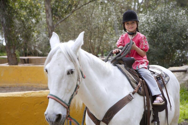 Des Jockeyhutes des kleinen Mädchens des Mitfahrers weißes Pferd im Park lizenzfreie stockbilder