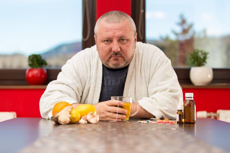 Des Kälte- und Wintergrippevirus des kranken Mannes leidender trinkender Tee stockfoto