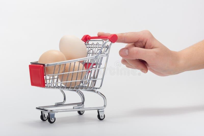 Des Käufers drückt einen Hühnerwagen mit einem Finger von Hand ein lizenzfreies stockfoto