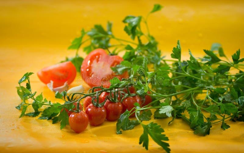 Des légumes - a coupé en tranches la tomate, tomates-cerises sur une branche, ail, persil photo stock