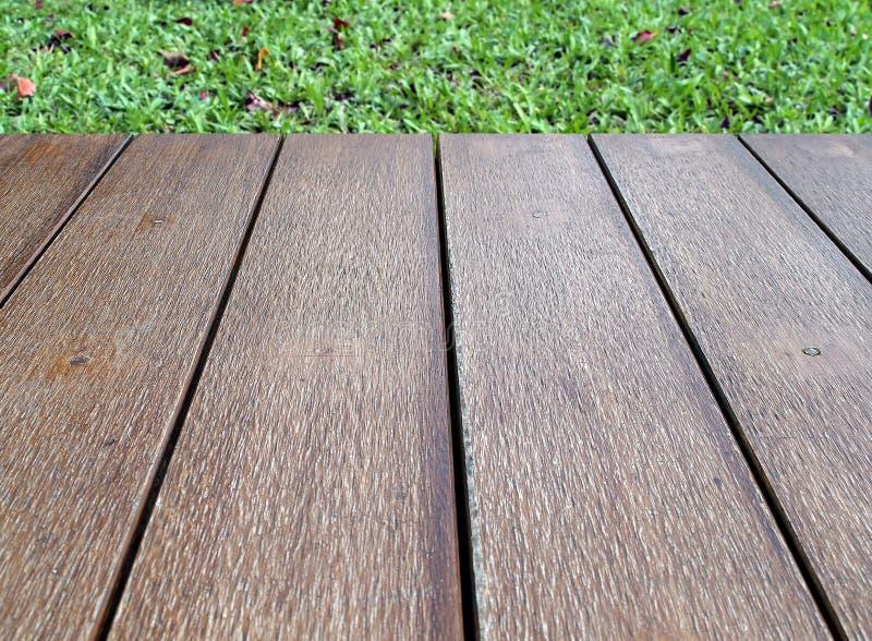 Des leeren hölzerne Bodenbelagterrasse Weinlesebrauns der Nahaufnahme mit grüner Rasenfläche lizenzfreie stockfotografie