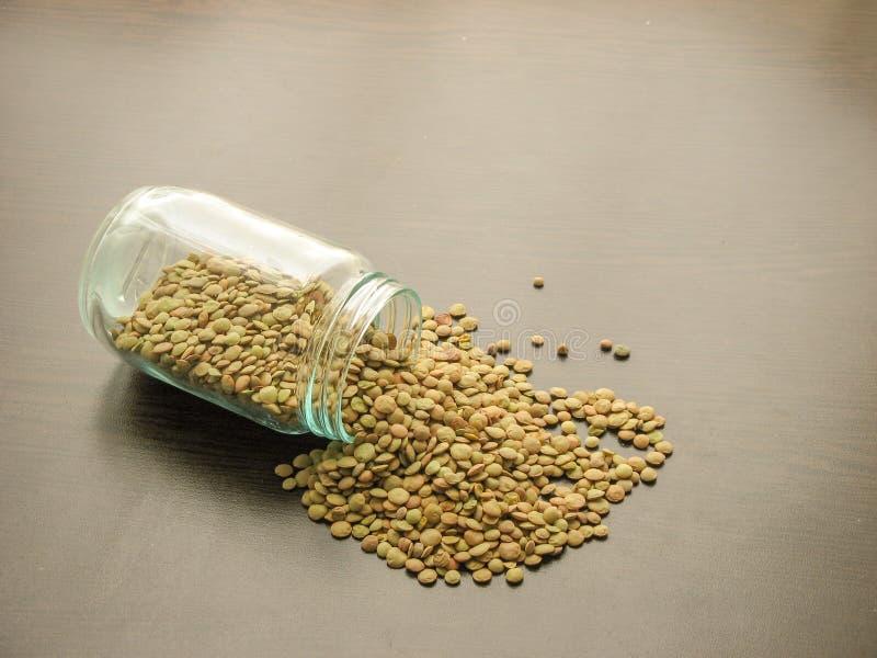 Des lentilles vertes sèches sont versées d'un pot en verre sur la surface en bois brune image libre de droits