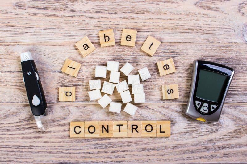 Des lettres en bois de bloc de gestion de diabète avec le mètre de sucre raffiné et de glucose sanguin, la valeur de sucre de san photographie stock