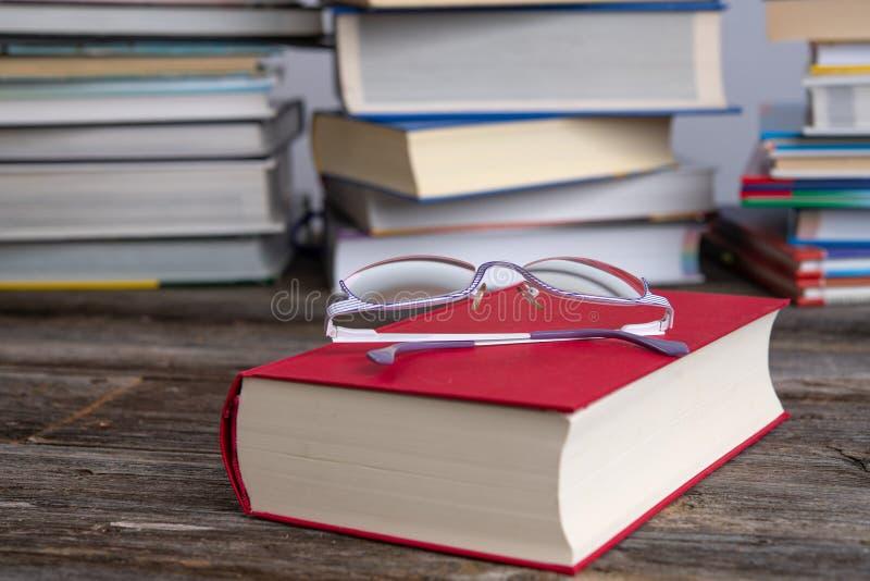 Des lunettes de lecture et de lecture devant des piles de livres différents photographie stock