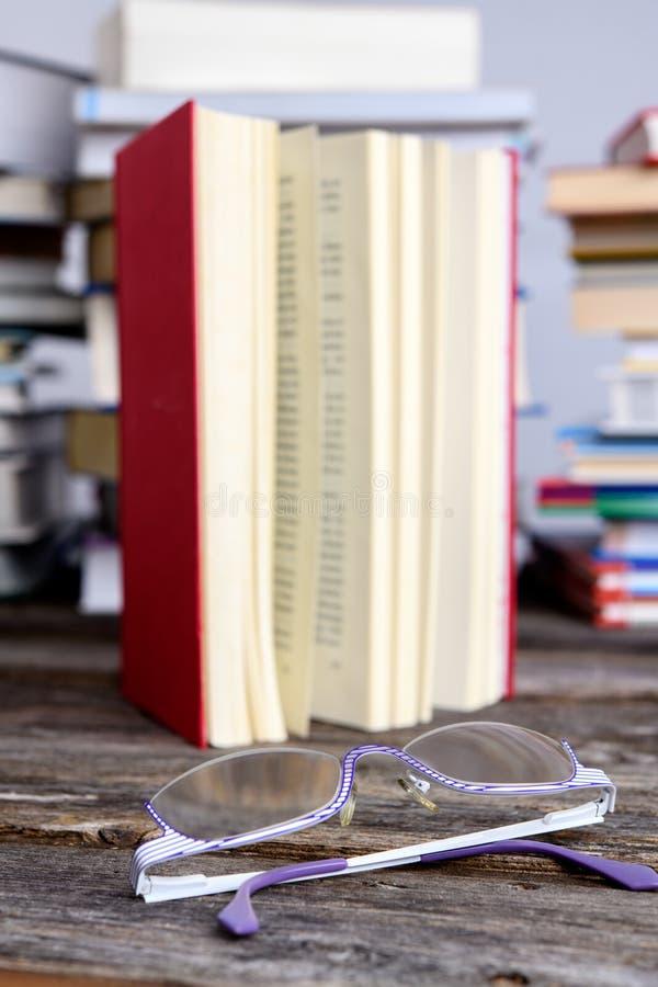 Des lunettes de lecture et de lecture devant des piles de livres différents photos libres de droits