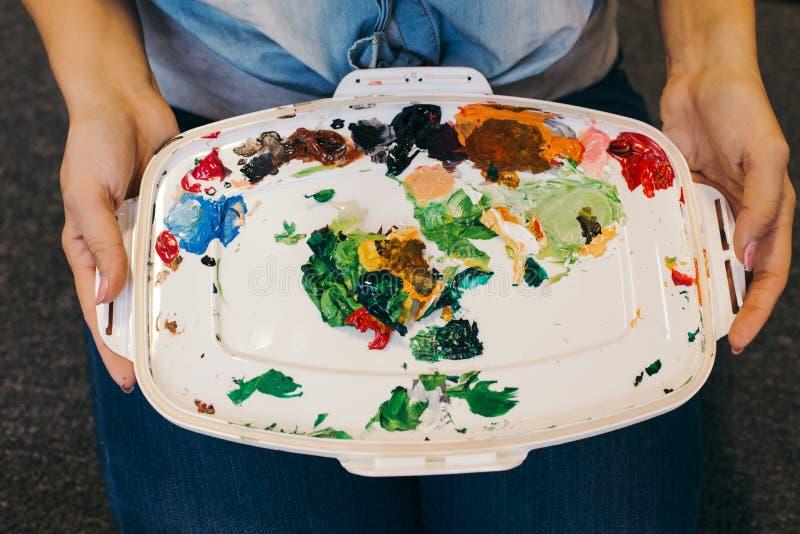 Des mains d'artiste tenant une palette sale et désordonnée avec différentes vieilles peintures acryliques sèches dans un studio d image libre de droits