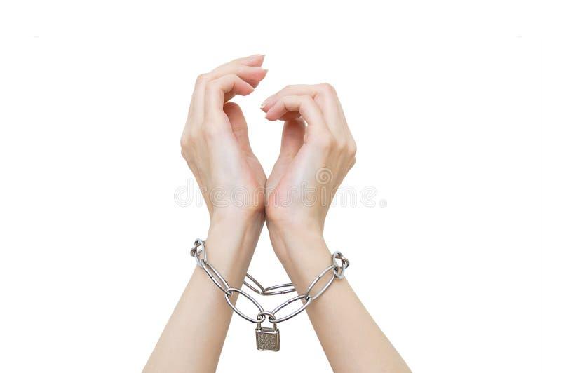 Des mains de femmes sont enchaînées et fermées à clef images stock