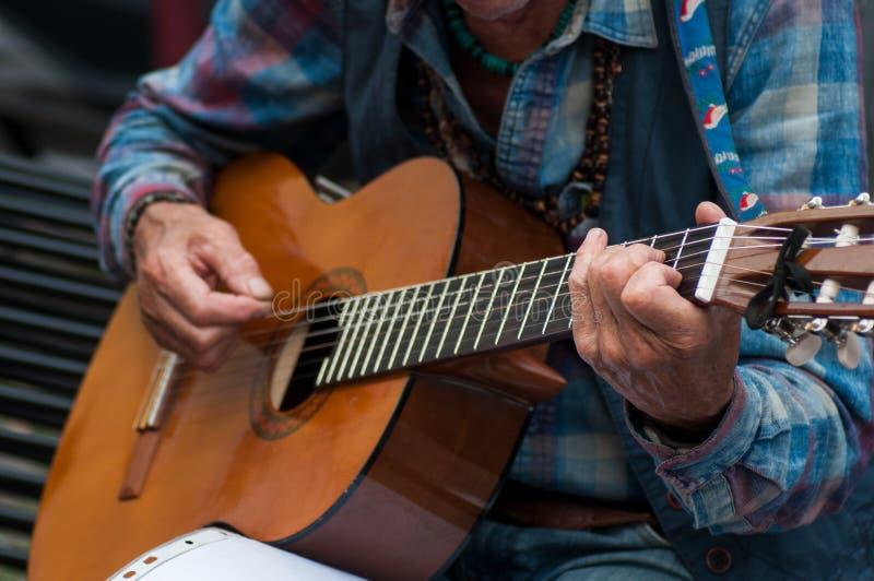Des mains de vieil homme jouant de la guitare acoustique dans la rue image stock