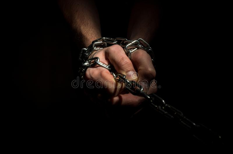 Des mains sont enchaînées dans les chaînes sur le fond noir photos libres de droits