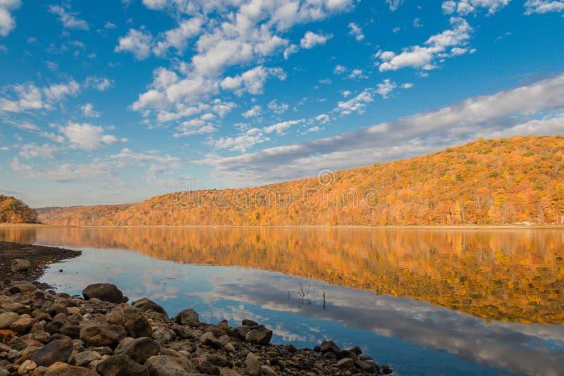 Des montagnes du feuillage d'automne vibrant est vues du rivage rocheux photos libres de droits