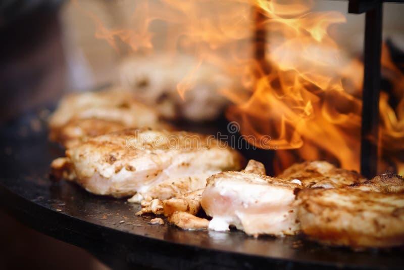 Des morceaux de poulet sont faits frire sur un feu ouvert dans l'extérieur photographie stock