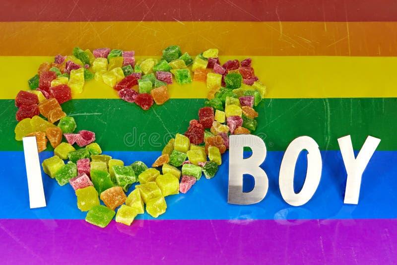 Des morceaux multicolores d'ananas secs sont présentés sous forme de coeur, et les lettres en métal j'aime le garçon, me trouve d photo libre de droits