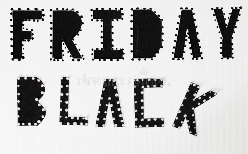 Des mots BLACK FRIDAY sont coupés du papier noir de carton image stock