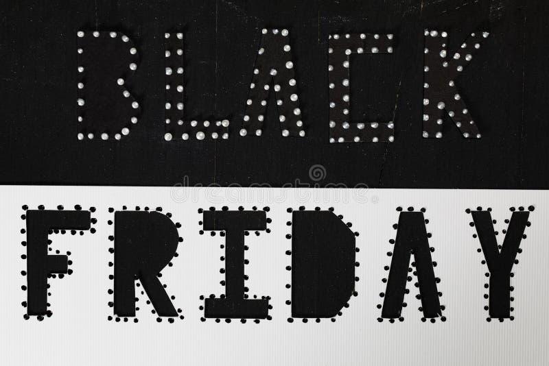 Des mots BLACK FRIDAY sont coupés du papier noir de carton photos stock