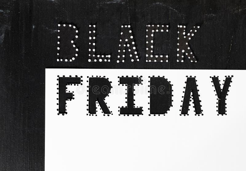 Des mots BLACK FRIDAY sont coupés du papier noir de carton images libres de droits
