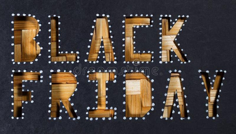 Des mots BLACK FRIDAY sont coupés du papier noir de carton image libre de droits