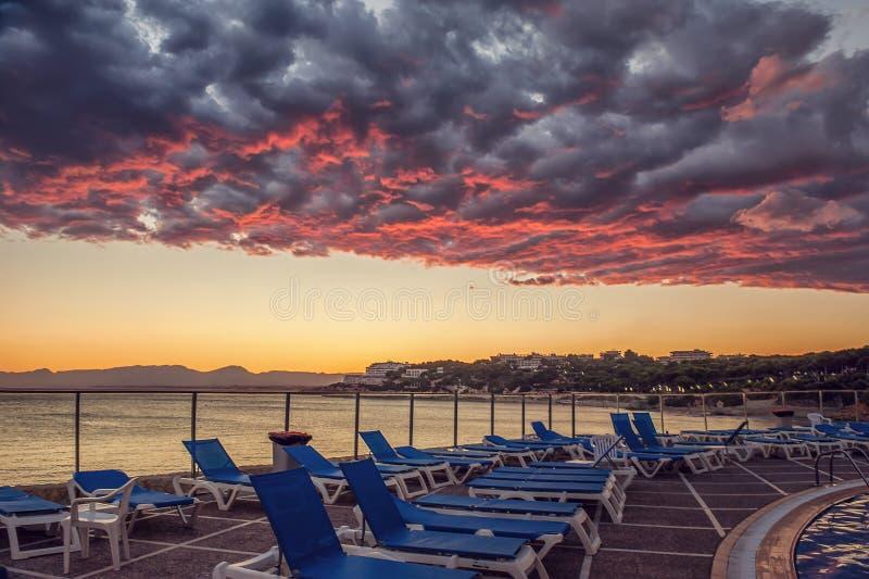 Des nuages dramatiques fantastiques au-dessus de la côte avec des canapés du soleil sont illuminés par le soleil de coucher du so photo stock