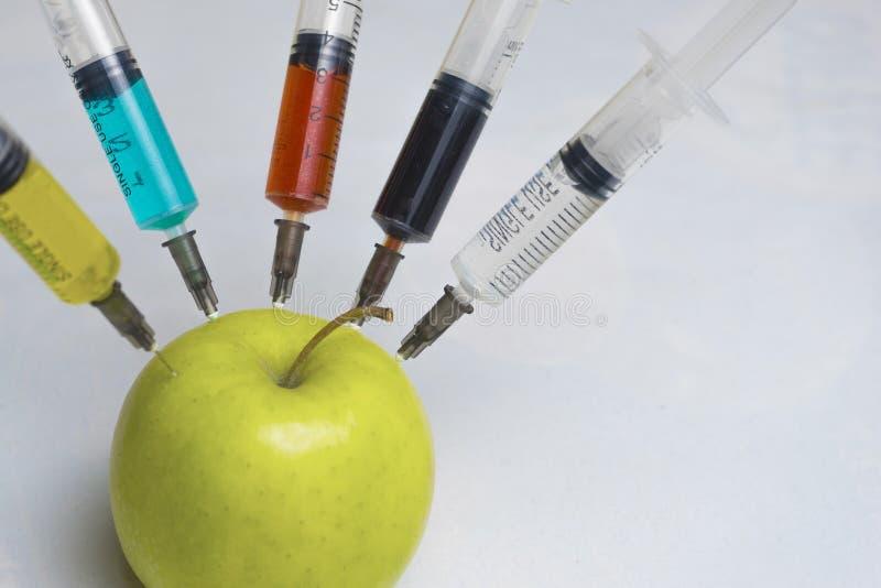 Des pesticides, les nitrates, les fongicides et d'autres produits chimiques sont injectés dans une pomme verte avec une seringue  photo libre de droits