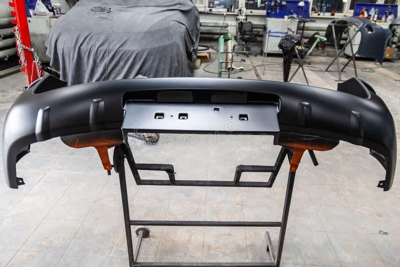 Des pièces de butoir automatiques est installées sur les supports après peinture dans l'atelier de réparations de voiture dan photographie stock libre de droits