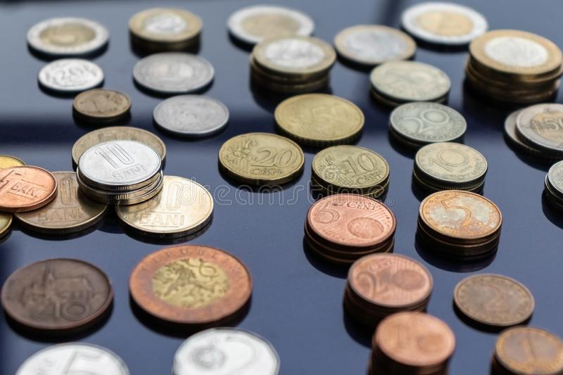 Des pièces de monnaie de différents pays sont présentées sur des piles sur un fond bleu images stock