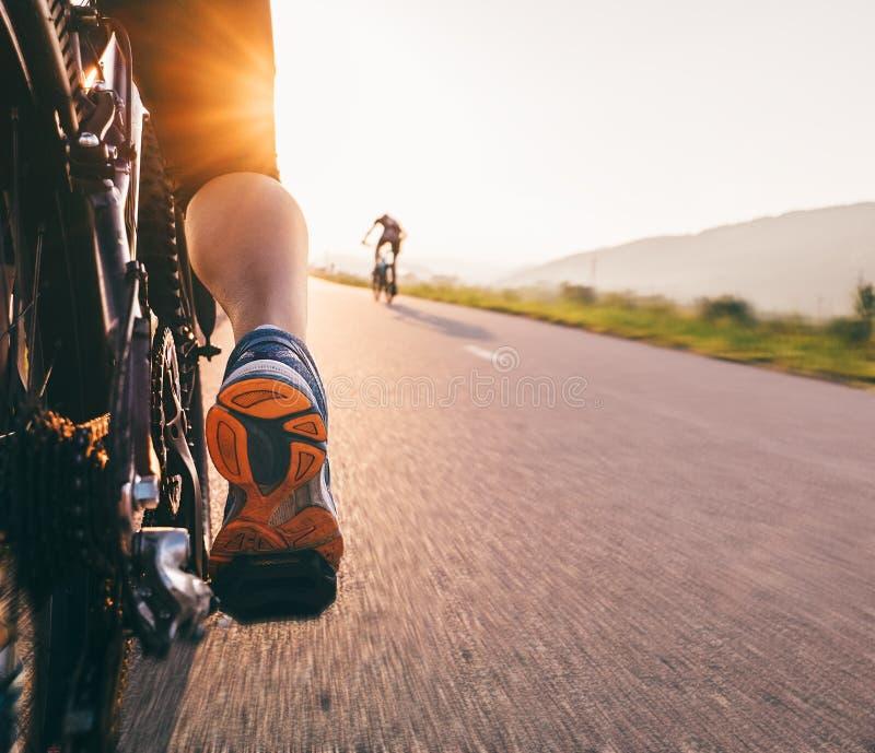 Des pieds sur la pédale de bycikle dans la lumière de coucher du soleil - fermez-vous vers le haut de l'image images stock