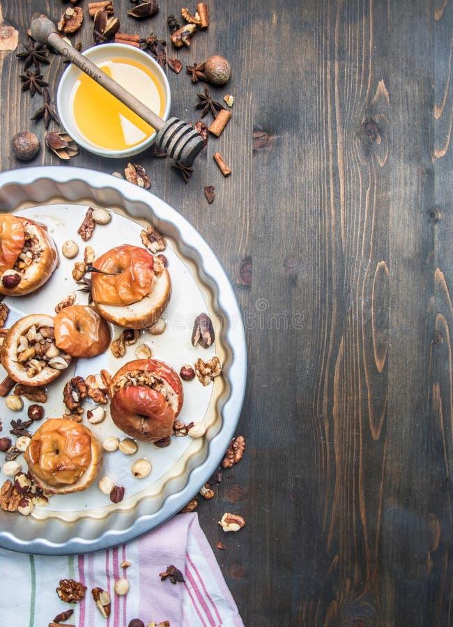 Des pommes cuites au four avec du miel et des écrous sur un plateau pour la cuisson, ingrédients sont étendues autour, serviette, image libre de droits