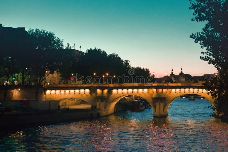 Des ponts de Paris au-dessus de la Seine sont bien illuminés la nuit photographie stock libre de droits